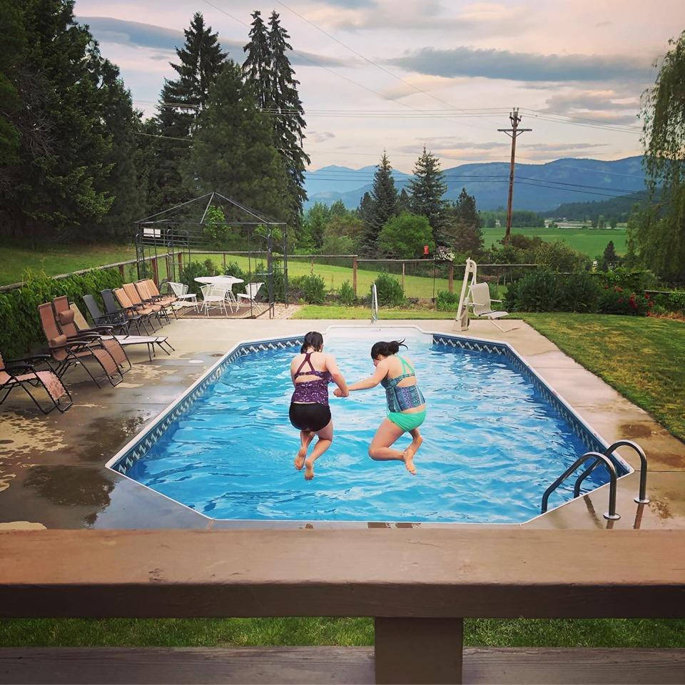 Two Girls Jumping Into Pool