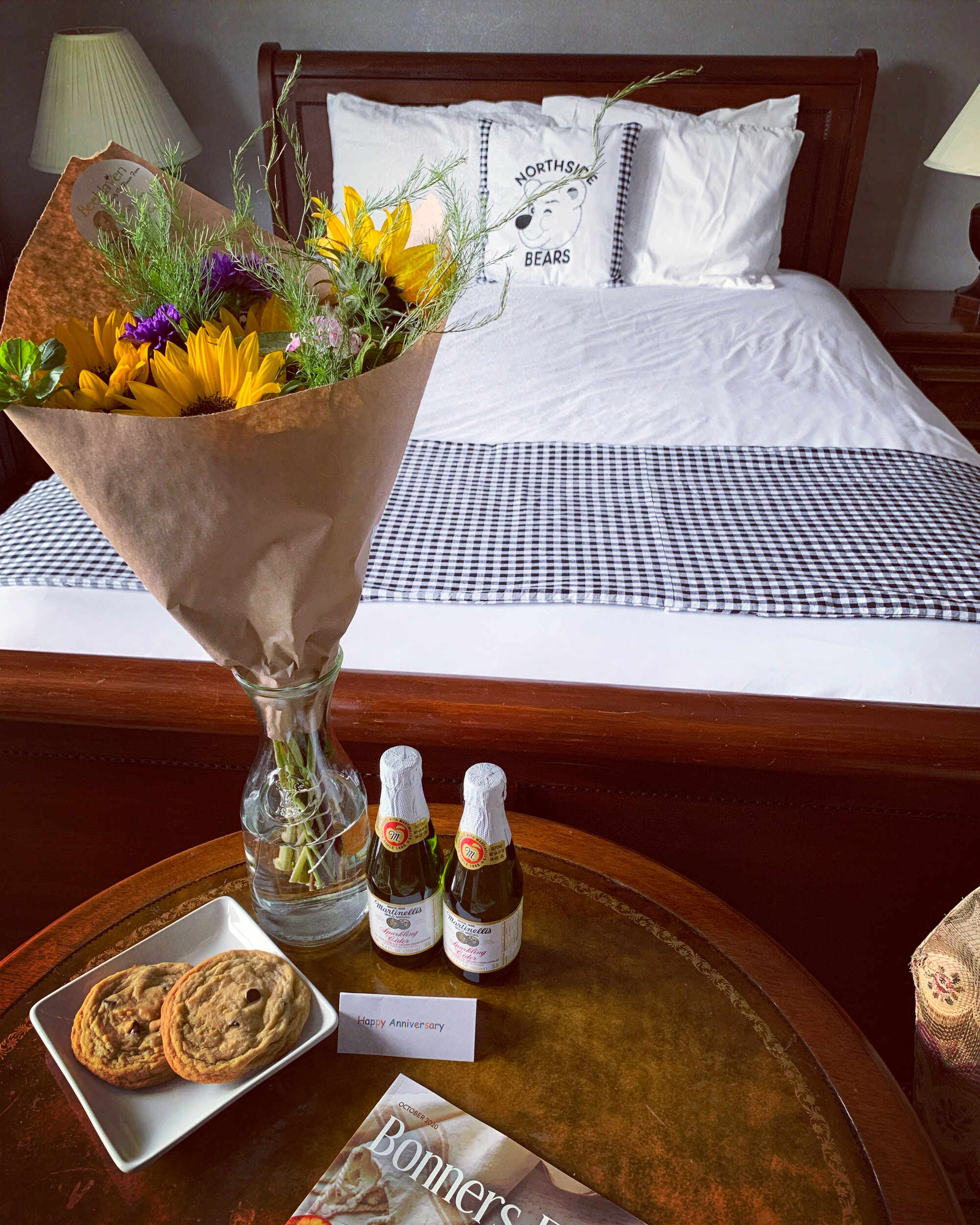 bed with flowers and treats on table
